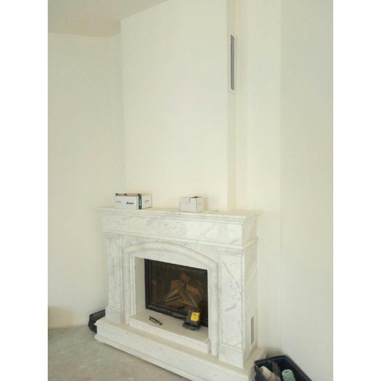 Угловой камин из белого мрамора в гостиной